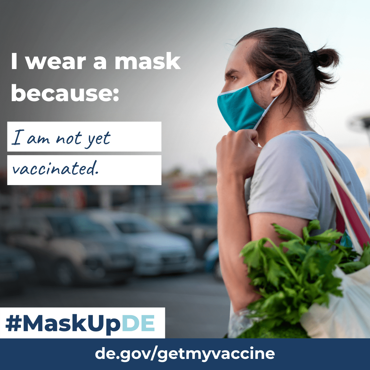 I wear a mask because...I am not fully vaccinated. A male walks out of a grocery store with a cloth face mask on.
