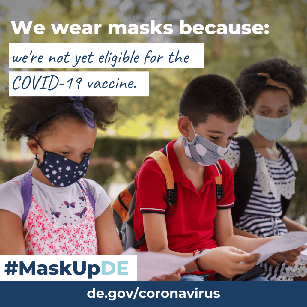 """three children sitting on a bench reading homework papers while wearing masks outside. The graphic elements read: """"We wear masks because: we're not yet eligible for the COVID-19 vaccine."""""""